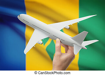 Airplane in hand with flag on background - Saint Vincent and...