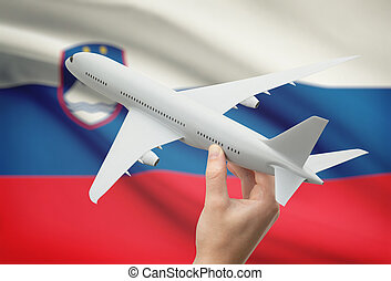Airplane in hand with flag on background - Slovenia -...