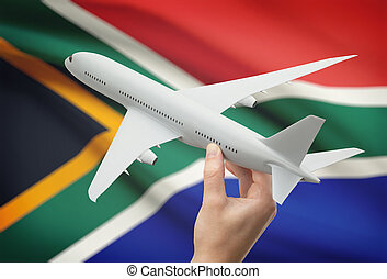 Airplane in hand with flag on background - South Africa -...