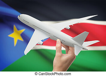 Airplane in hand with flag on background - South Sudan -...