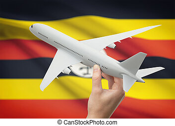 Airplane in hand with flag on background - Uganda - Airplane...