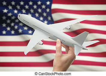 Airplane in hand with flag on background - United States -...