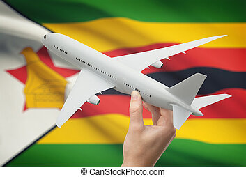 Airplane in hand with flag on background - Zimbabwe -...