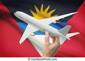 Airplane in hand with flag on background - Antigua and...
