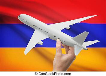 Airplane in hand with flag on background - Armenia -...