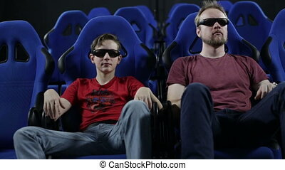 Man and teen boy watching movie in cinema 5d - Man (father)...