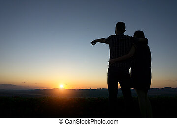 silhouette lovers Hands up against sunset time with lens...