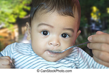 Eating from spoon of six month asian baby