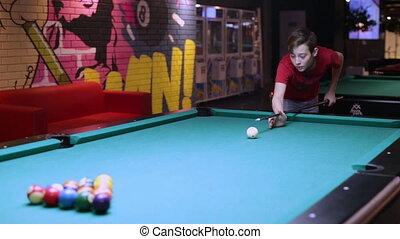 Teenager boy man in billiards shoots at balls