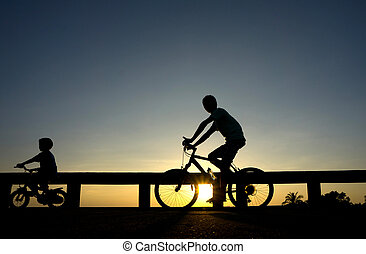 Silhouette motion cyclist bicycles against sunset