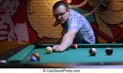 Man playing pool, sending ball in the hole