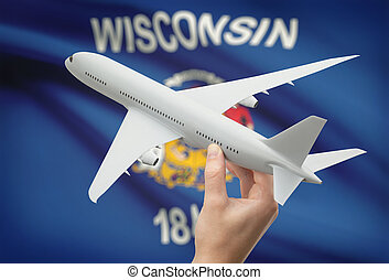 Airplane in hand with US state flag on background -...