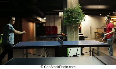 Two male friends playing a game of ping pong