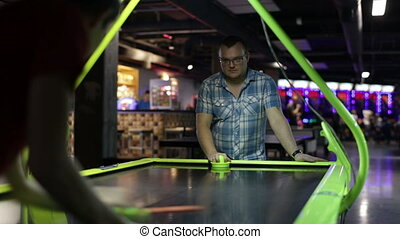 Adult man playing air hockey - Young adult man playing air...