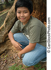 little boy sit down beside the tree - little asian boy sit...