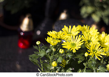 Yellow flowers on a grave with candle