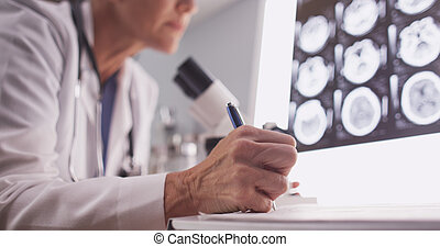 Intelligent female radiologist analyzing with microscope