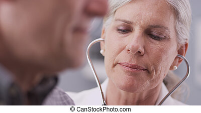 Mid-aged doctor listening to heart - Mid-aged doctor talking...