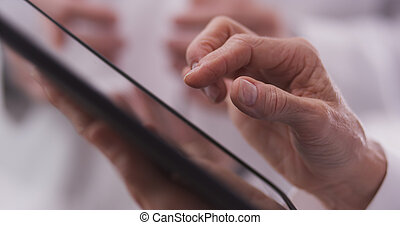 Elderly doctor typing on tablet - Close-up of middle-aged...