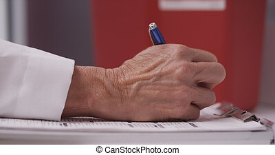 Doctors hand writing notes