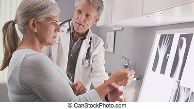 Senior doctor assessing injury - Senior male doctor...