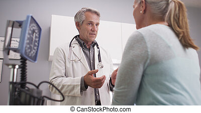 Mid-aged doctor talking to patient - Mid-aged doctor talking...