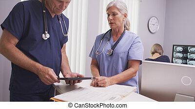 Mature medical practitioners talkin - Mature female medical...