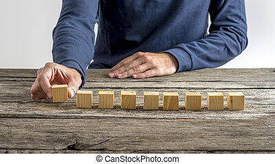 Front view of male hand placing nine blank wooden cubes in a...