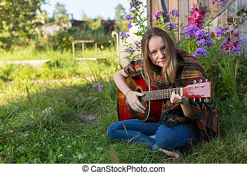 Young girl playing acoustic guitar sitting outdoors