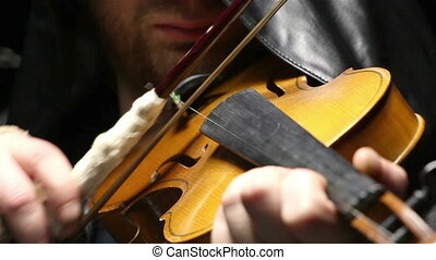 Man in hood playing the fiddler, video on black background