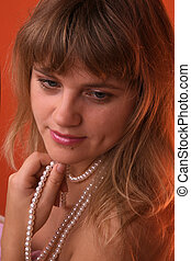 Sexy young woman with a pearl necklace over red background