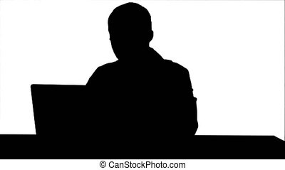 Silhouette Concentrated male doctor using laptop at medical...