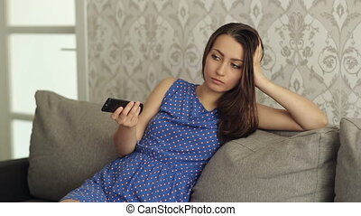 Woman With TV Remote Switcing Boring TV Channels - Woman...