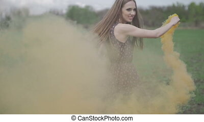 Happy young woman in dark dress with floral print having fun outdoor in geen field. Beauty girl with orange smoke bomb spinning and laughing.wonderful smile. green background colorful smoke. ungraded flat color slow motion
