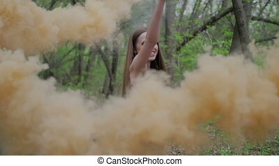 Happy young woman in dark dress with floral print having fun outdoor in summer forest. Beauty girl holding a colorful orange smoke bomb.wonderful smile. camera follow middle shot slow motion
