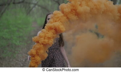 Happy young woman in dark dress with floral print having fun outdoor in summer forest. Beauty girl holding a colorful orange smoke bomb and goes to the camera.wonderful smile. middle shot slow motion ungraded flat color