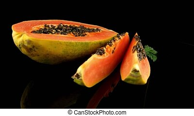 Slices of sweet papaya on black background
