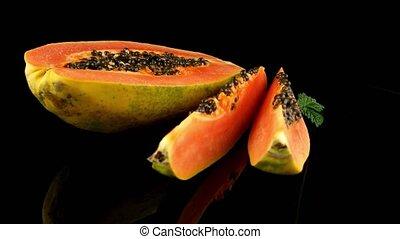 Slices of sweet papaya on black background.