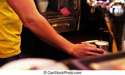 The barman at the bar counter prepares coffee using the...