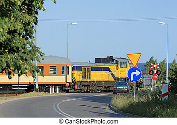 Railroad crossing with passing train - Passenger train...