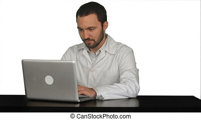 Concentrated male doctor using laptop at medical office on...