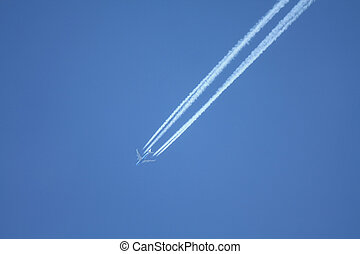 Contrails in the sky - Four engine airplane leaving...