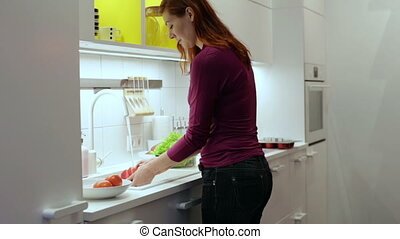 Woman washing red pepper in the kitchen sink