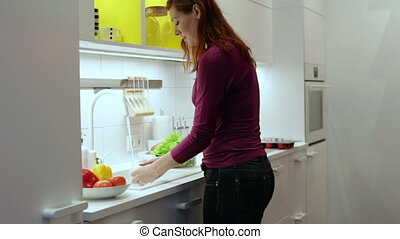 Woman washes a lemon and cucumber in the sink