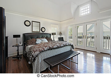 Master bedroom in luxury home with balcony