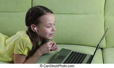 Emotional little girl talking on Skype at laptop - Emotional...