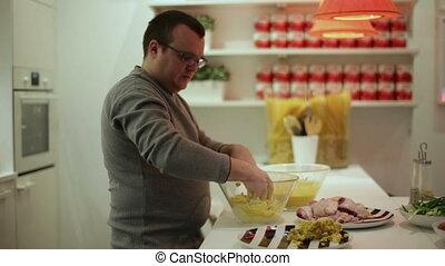Man prepares chicken in batter