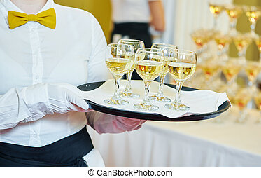 Waiter holding a tray with glasses of vine - catering or...