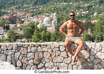 Man Showing His Well Trained Body Outdoors - Portrait Of A...