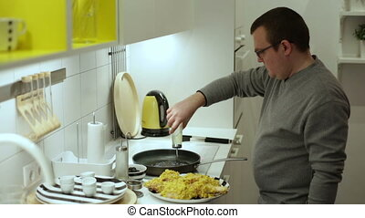 Man pours sunflower oil in a frying pan on the stove...
